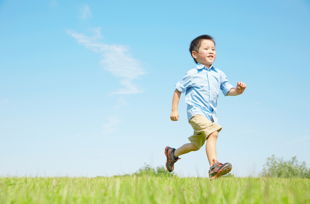 快晴の外を走る男の子