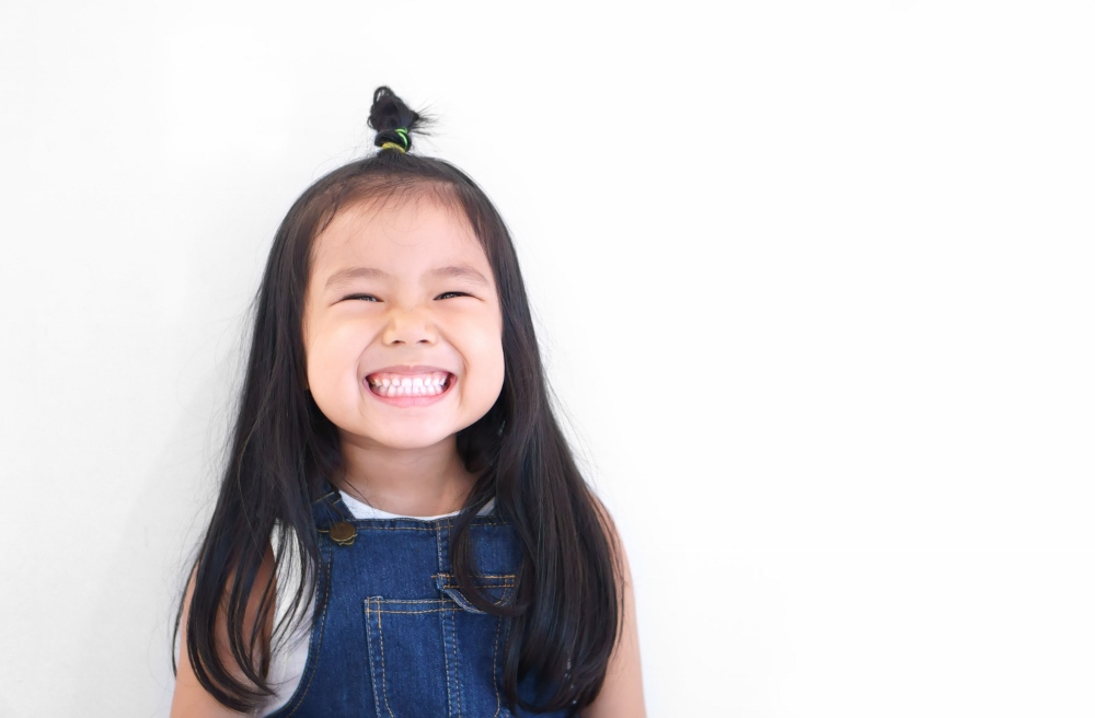 Asian children cute or kid girl and kindergarten student happy smile white teeth and laugh with wear dungarees jean for fashion on white background with space isolated